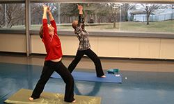 Two adult women performing a yogalates pose.